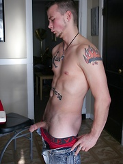 Tattooed Kyle Collins stroking his small cock.